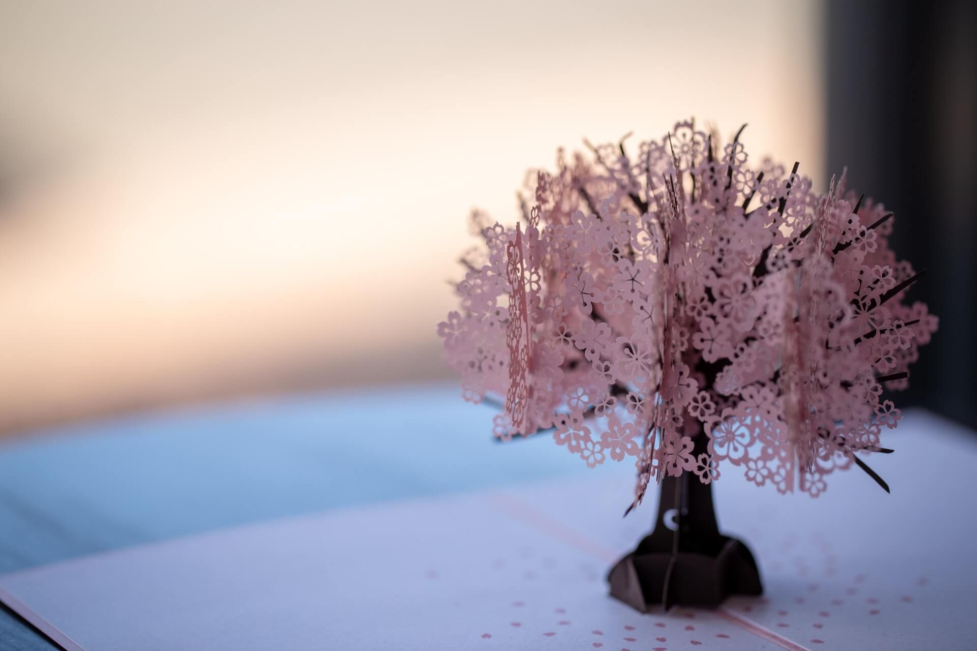 A paper model of a tree with pink blossom