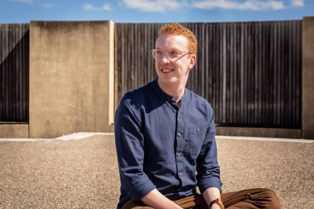 Mark Grainger of Blossom Tree Copy Agency sitting face on in front of a wooden fence