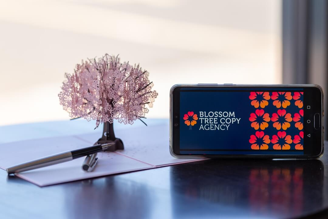 Paper blossom tree next to iPhone with the agency logo on its screen